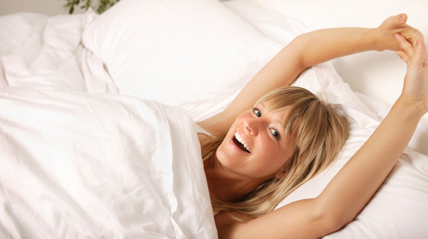 happy-woman-stretching-in-bed
